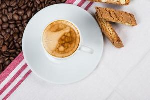 kopje romige espresso over gebrande koffiebonen foto