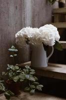 witte bloemen in witte keramische vaas foto