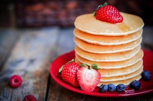 zelfgemaakte pannenkoeken met aardbeien, bosbessen en ahornsiroop op achtergrond foto