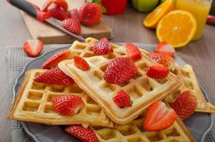 huisgemaakte wafels met ahornsiroop en aardbeien foto
