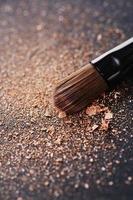 poeder verspreid op zwarte achtergrond van make-up borstel