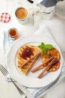 Franse toast met sinaasappelmarmelade, gegrilde appels en kaneelstokjes. foto