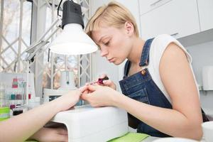 blonde schildert nagels in uv-lamp