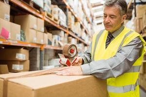 magazijnmedewerker verzegelt kartonnen dozen voor verzending foto