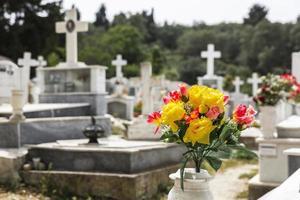 plastic bloemen op een griekse begraafplaats foto