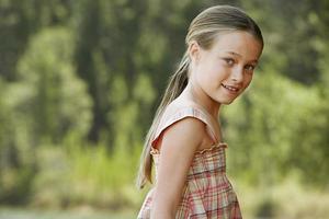 jong meisje permanent buitenshuis foto