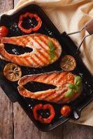 zalm steaks en groenten op grill close-up. verticaal bovenaanzicht foto
