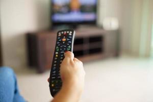 vrouw zitten kijken naar tv veranderende kanaal met afstandsbediening
