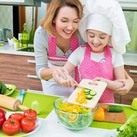 glimlachende moeder en dochter die een salade koken. foto