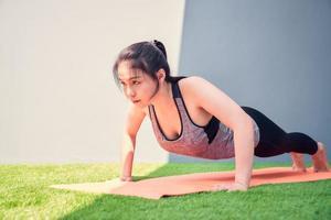 vrouw oefenen push-ups op een trainingsmat buiten