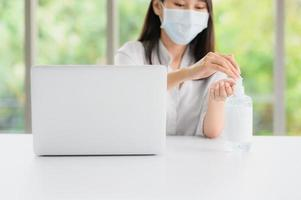 vrouw die een gezichtsmasker draagt met ontsmettingsmiddel naast de computer