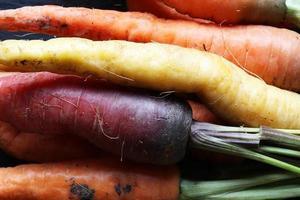 ongewassen kleurrijke wortelen voor voedselachtergrond foto
