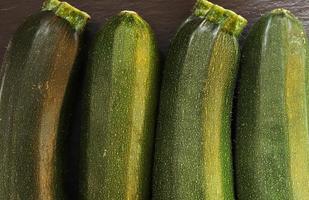 vier courgettes voor voedselachtergrond foto