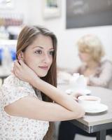 doordachte jonge vrouw met koffie in café foto