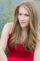 portret van jonge mooie blonde meisje buiten zitten, peinzende blik foto