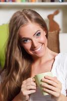 mooie jonge vrouw die een kopje thee drinkt foto