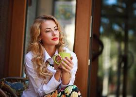 nadenkend vrouw zitten met koffiekopje buitenshuis foto