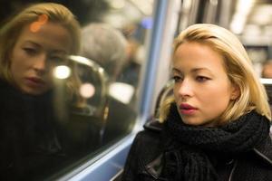 vrouw kijkt uit het raam van de metro.