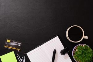 notitieboekje, creditcard en een koffiemok op het bureau