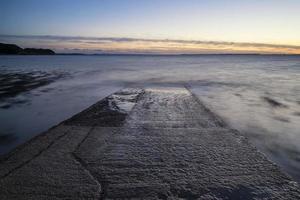 lange blootstelling landschapsbeeld van pier bij zonsondergang in de zomer