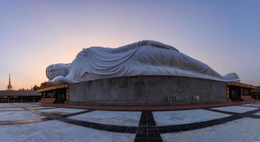 witte liggende Boeddha tijdens zonsondergang, thailand foto