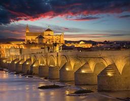Cordoba - Romeinse brug en de kathedraal in de schemering foto