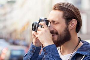 aantrekkelijke bebaarde man maakt foto's van de stad