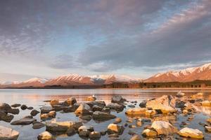 zonovergoten stenen op zonsondergang, Lake Tekapo, Nieuw-Zeeland