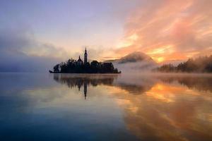 mistige zonsopgang op het meer bloedde in de herfst foto