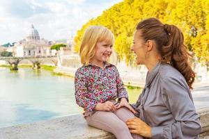 gelukkige moeder en babymeisje op brug ponte umberto i foto