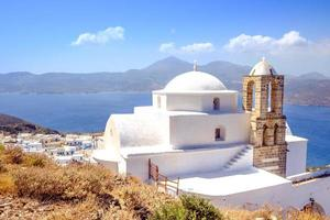 schilderachtig uitzicht op de traditionele Griekse Cycladische kerk, het dorp en de zee