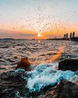 golven die tijdens zonsopgang op de kust breken foto
