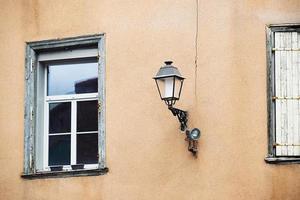 bruin gepleisterde muur met lantaarnpaal