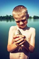 jonge jongen die een vis houdt.