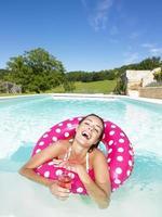 lachende vrouw in zwembad met drank foto