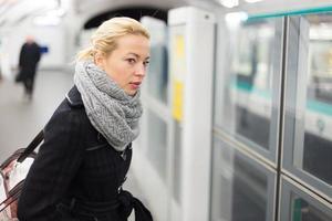 jonge vrouw op perron van metrostation.