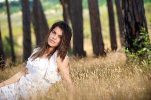 mooie jonge vrouw zittend in het gras op het platteland foto