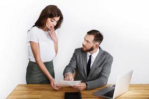 vrouw kijkt geschokt terwijl boze zakenman naar papier wijst