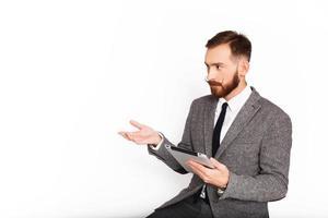 serieuze man in grijs pak gebaren terwijl hij een tablet vasthoudt