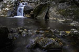 waterval die in rotsen stroomt foto