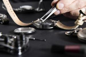 detail van horlogemaker die batterij vervangt foto