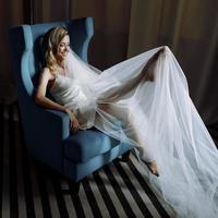 bruid steekt haar benen omhoog zittend in een grote blauwe stoel in hotelkamer