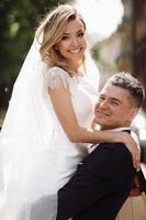 bruid en bruidegom omhelzen in de zon