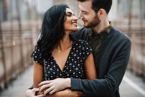 aantrekkelijk paar omhelst op stadsbrug foto
