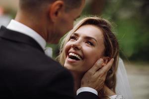 bruidegom houdt bruid tender in zijn armen terwijl ze naar hem kijkt met liefde foto