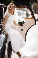 prachtige bruid in luxe witte jurk stapt uit een retro auto