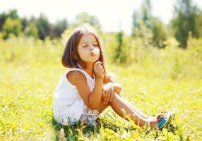 schattig klein meisje kind blaast paardebloem bloem in zonnige zomer