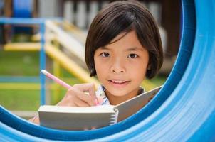 schattig klein meisje studeren op school en glimlachen foto