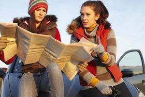 vrouwen die de kaart met de auto lezen