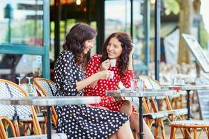 mooie tweelingzusjes die koffie drinken in parijs